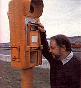 Man                         demonstrating use of an old-style emergency phone